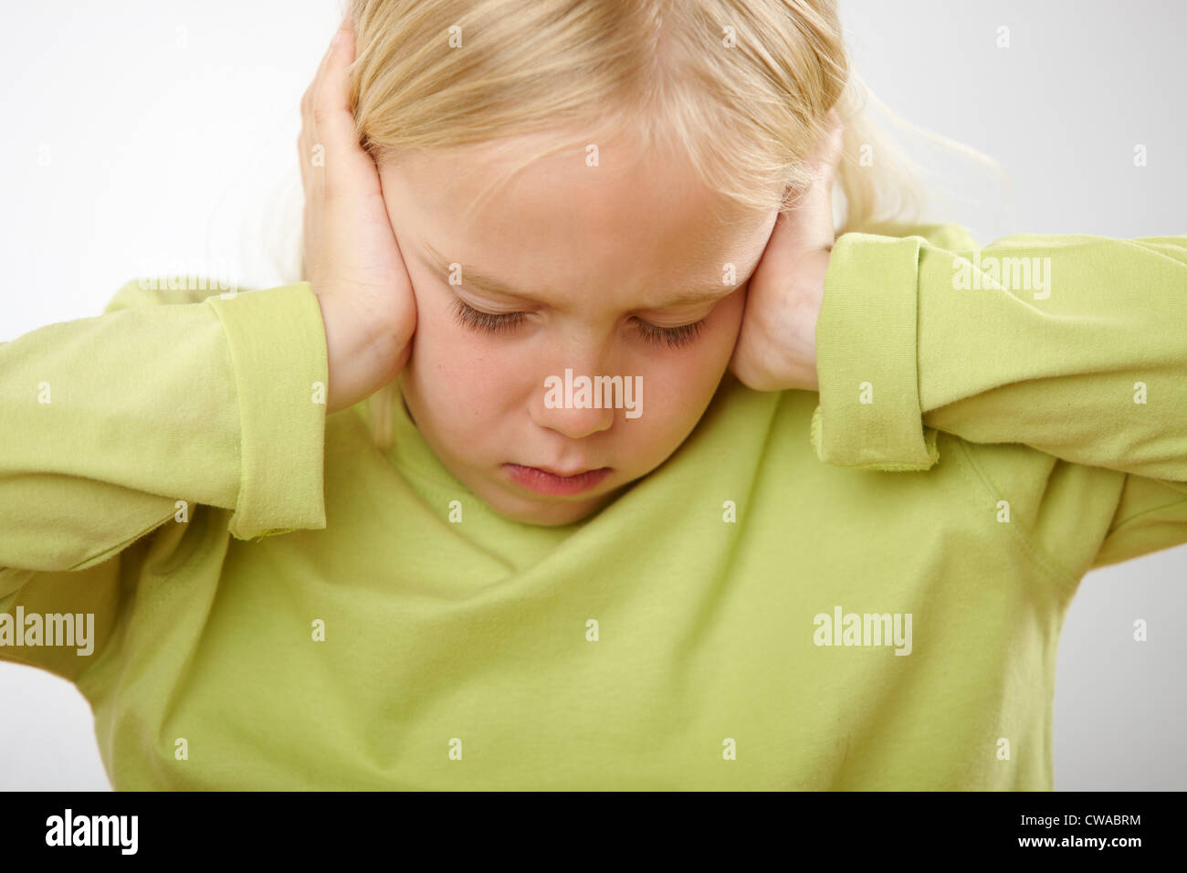 Girl with hands over ears - Stock Image