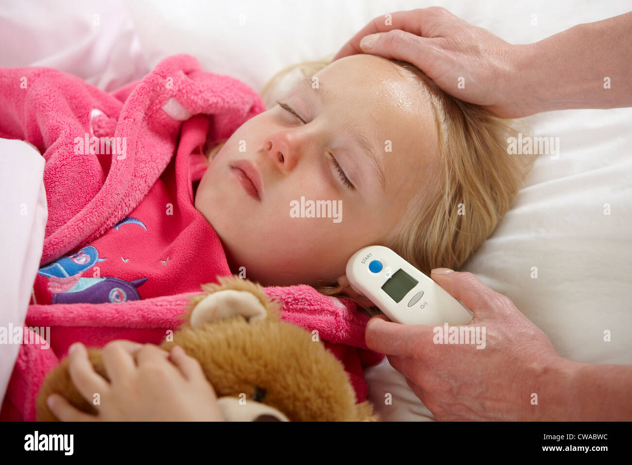 Parent taking daughter's temperature Stock Photo
