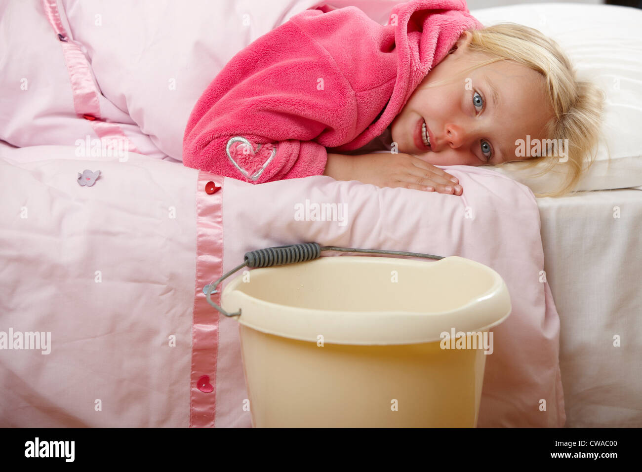 Ill girl in bed with bucket - Stock Image