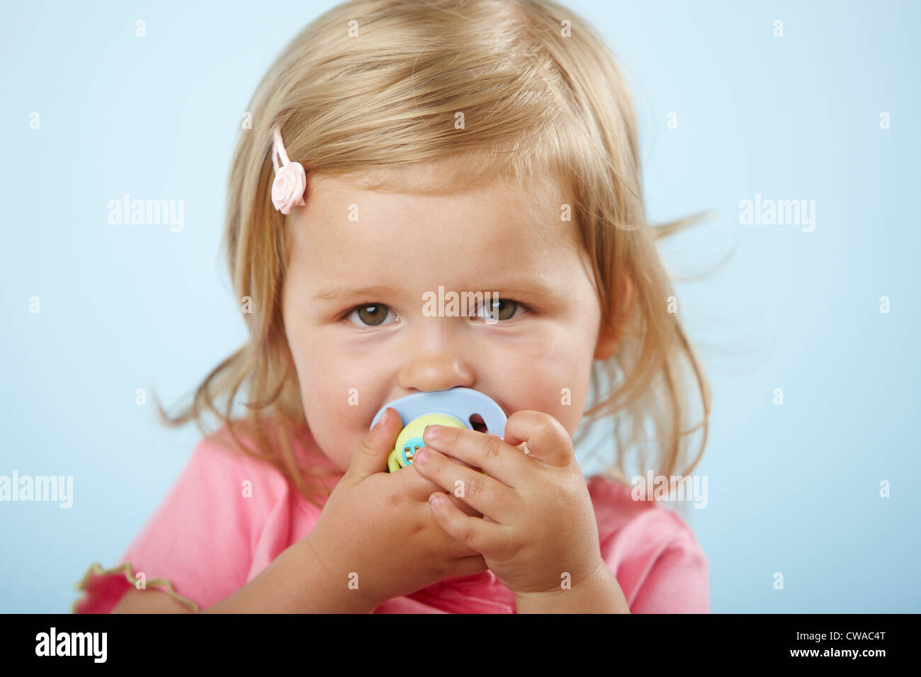 Girl with pacifier in mouth Stock Photo