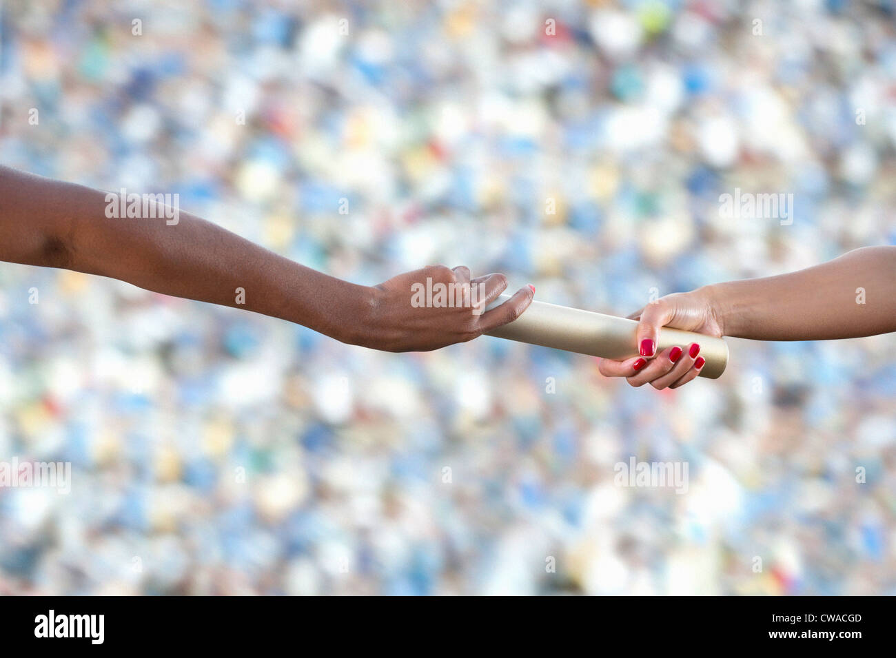 Relay athletes passing a baton, close up - Stock Image