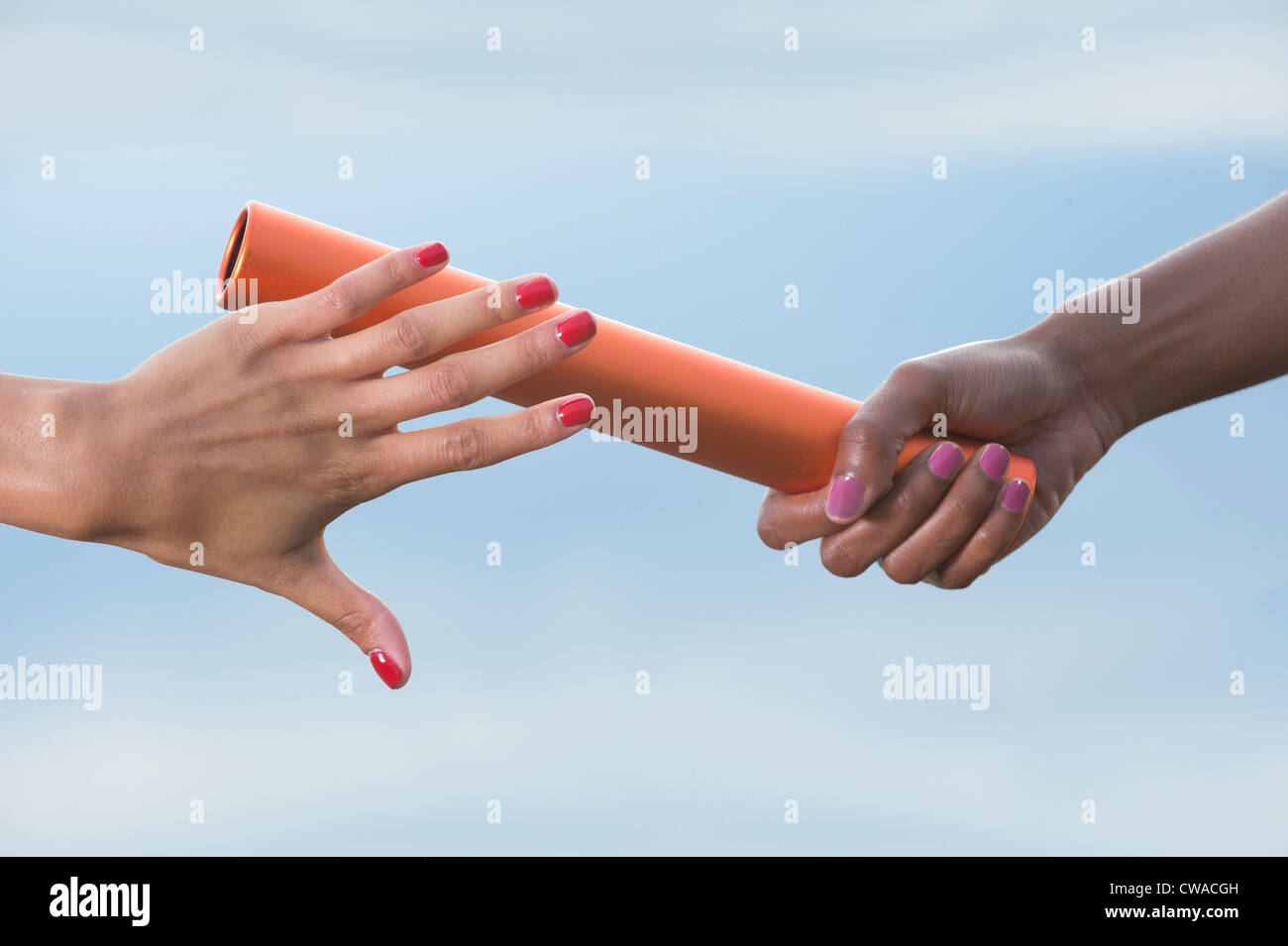 Hands of female relay athletes passing a baton, close up Stock Photo