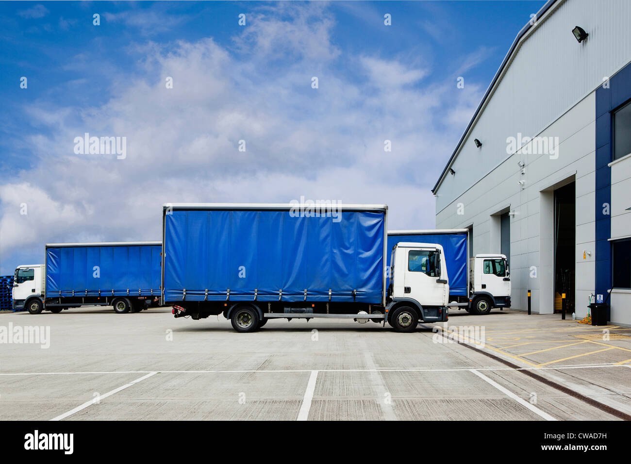 Trucks parked outside distribution warehouse - Stock Image
