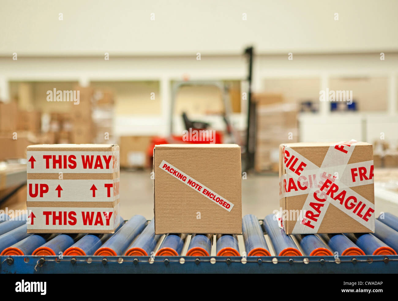 Three cardboard boxes with parcel tape on conveyor belt - Stock Image