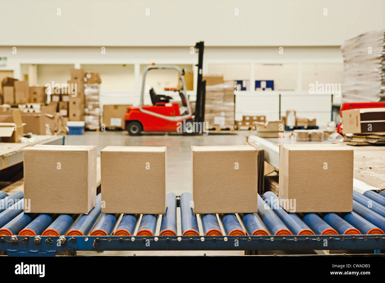Four cardboard boxes on conveyor belt - Stock Image