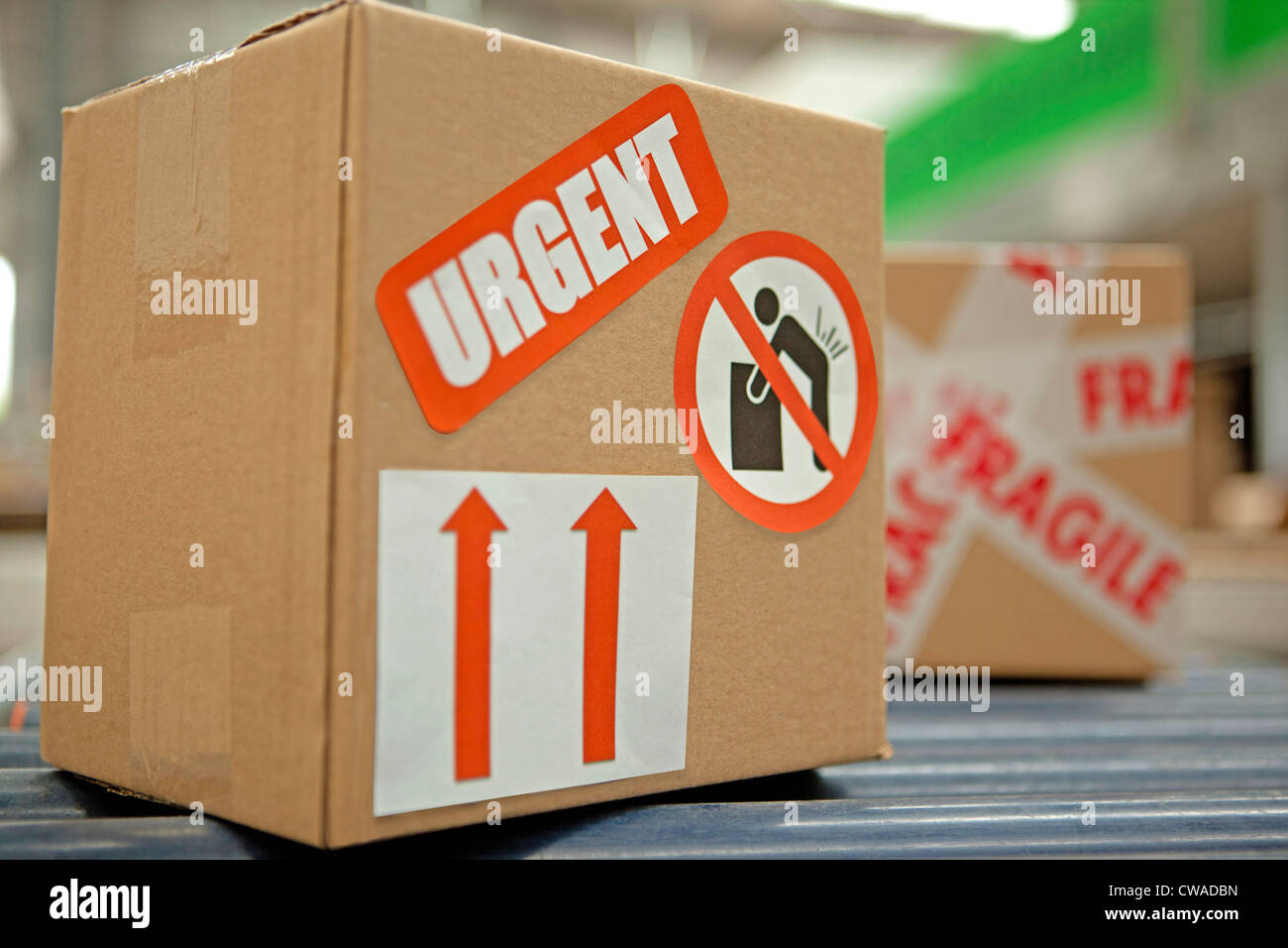 Cardboard box with warning stickers on conveyor belt - Stock Image