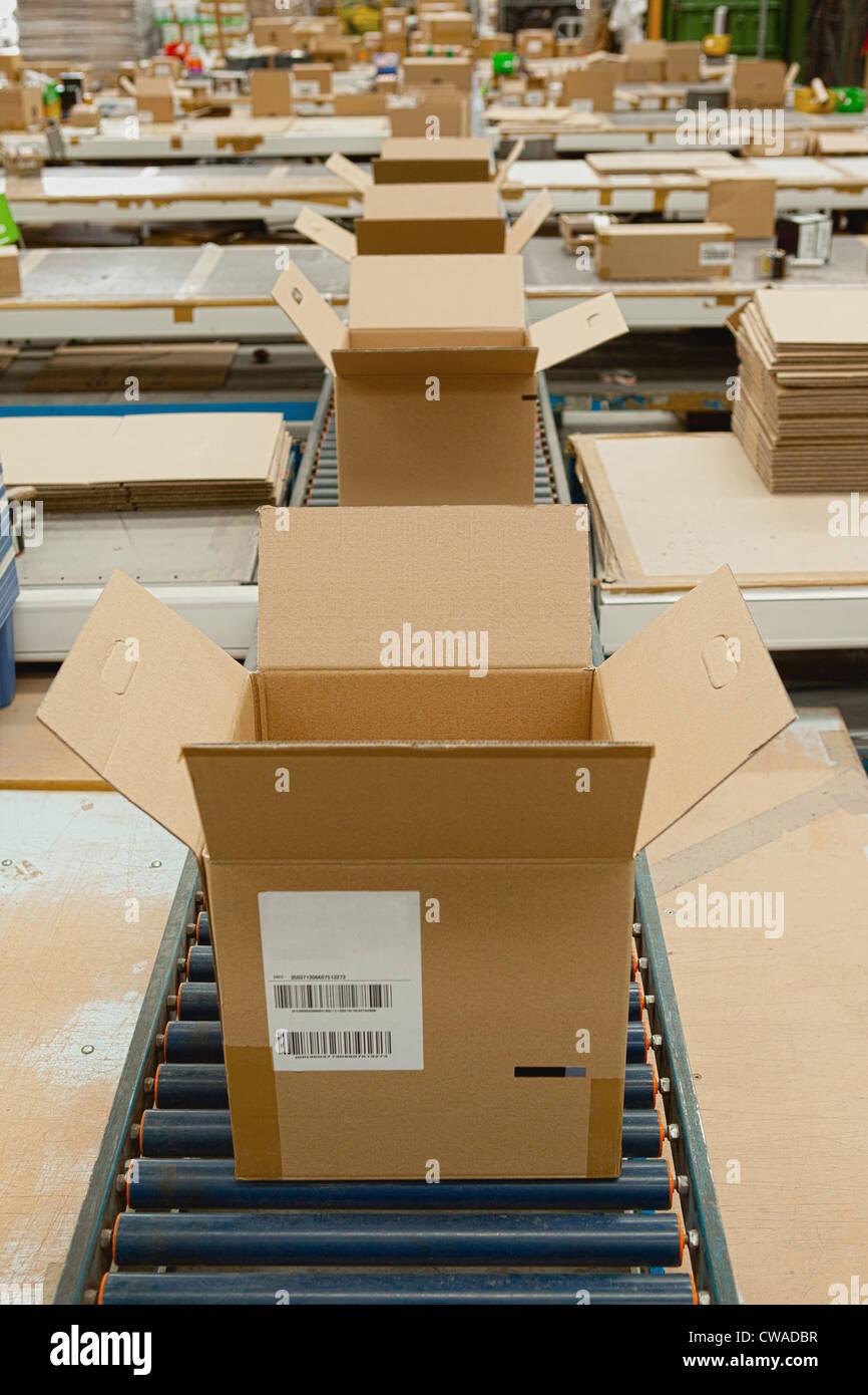 Open cardboard boxes on conveyor belt - Stock Image