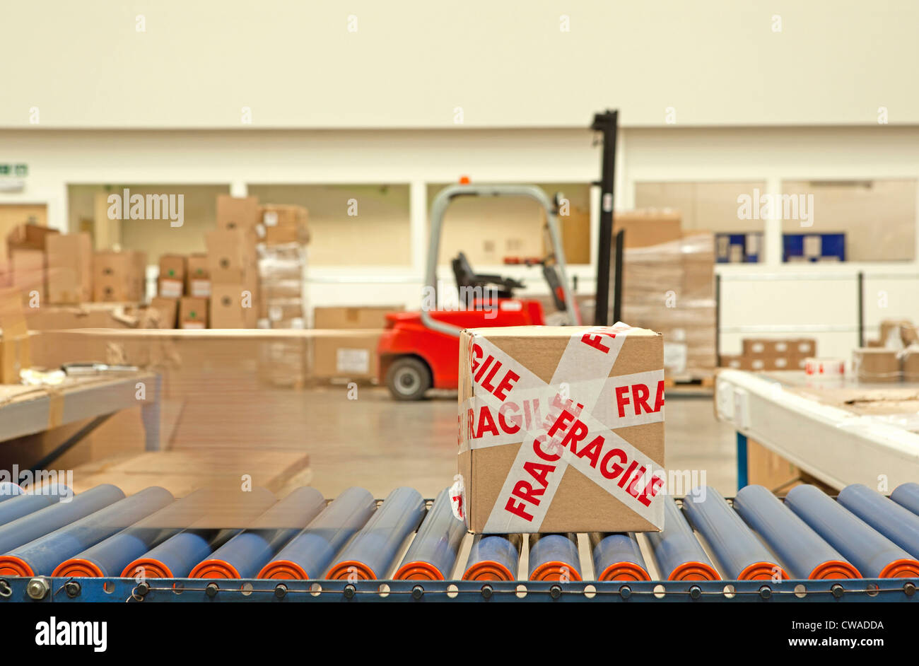 Box with fragile tape on conveyor belt - Stock Image