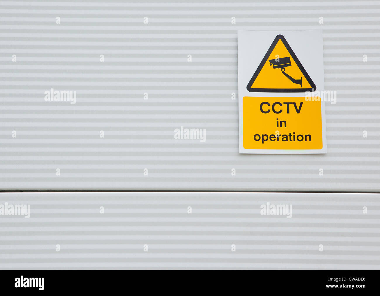 Surveillance camera sign on warehouse door - Stock Image