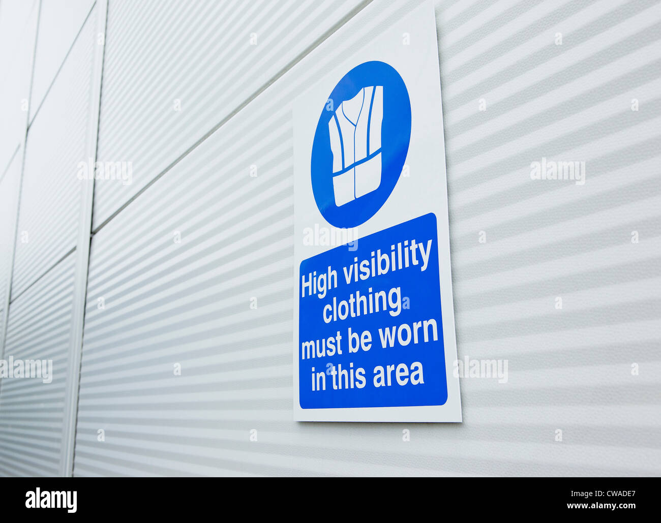 High visibility clothing sign on warehouse door - Stock Image