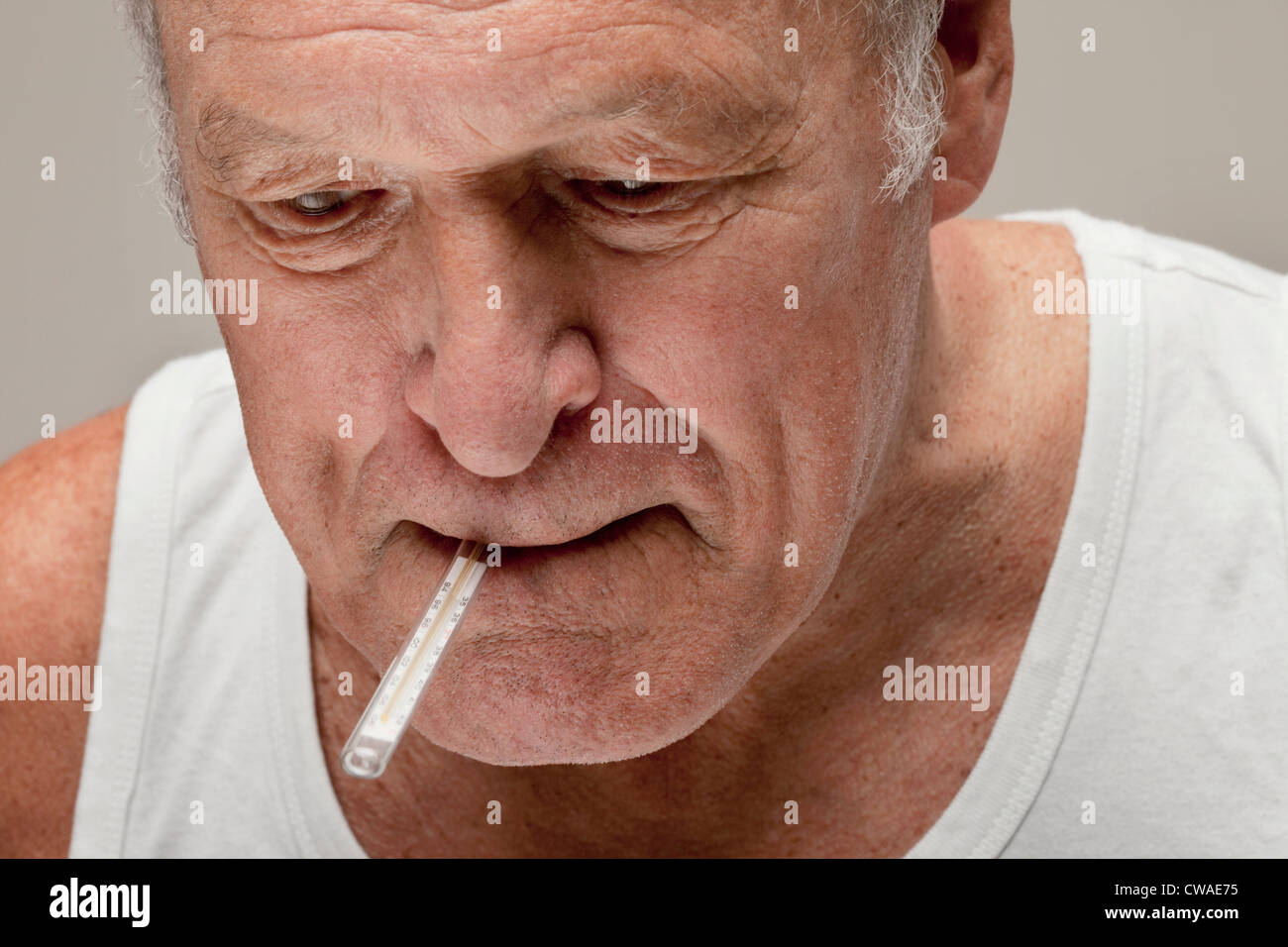 Senior man with thermometer in mouth - Stock Image