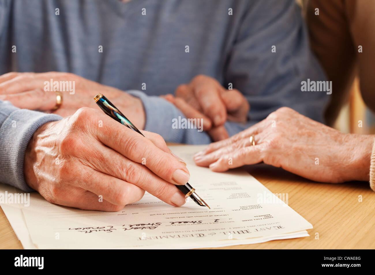 Senior man signing will - Stock Image