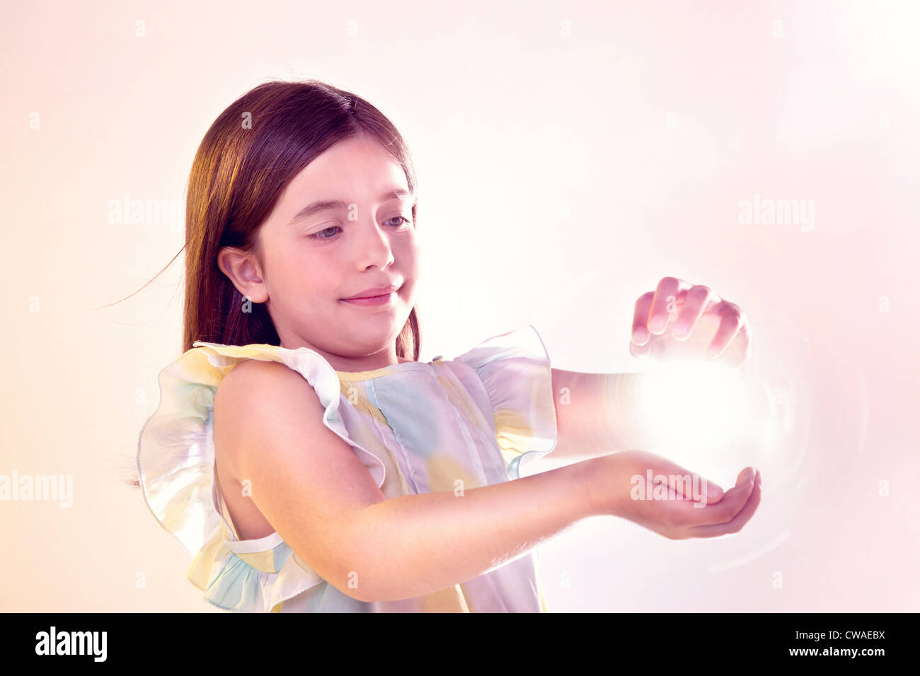 Girl holding a ball of light - Stock Image