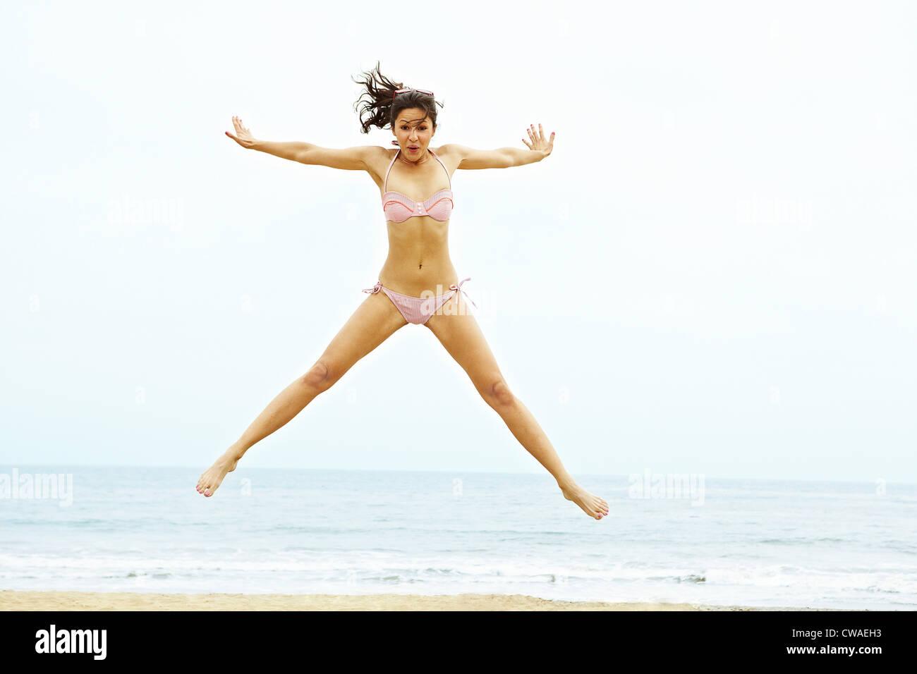 Young woman in bikini doing star jump on beach - Stock Image