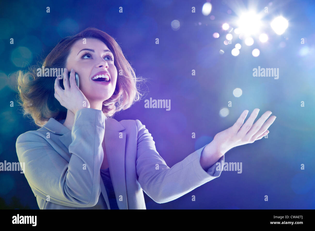 Young woman on cellphone, looking up at lights - Stock Image