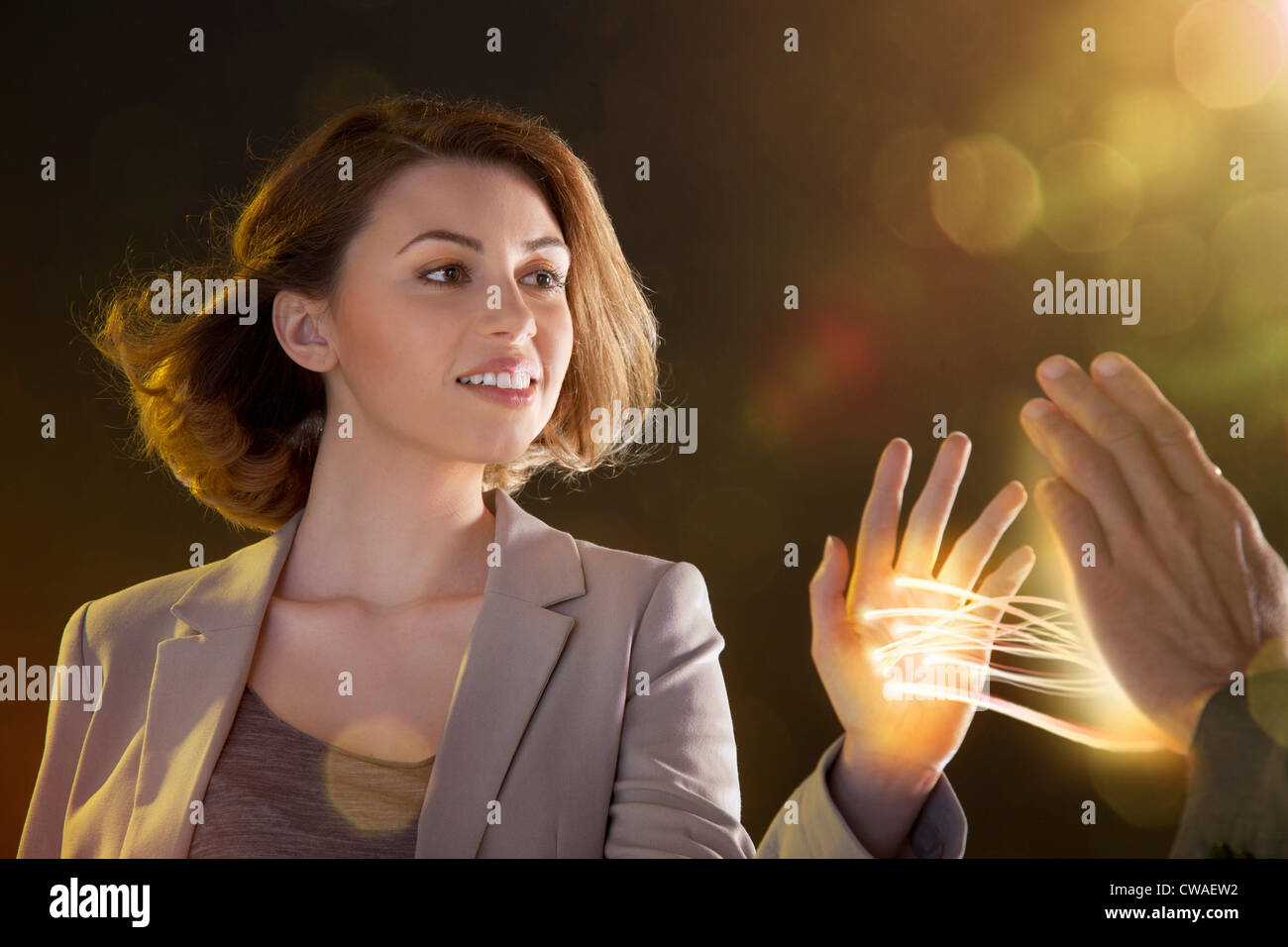 Young woman touching light streams, connecting to another person - Stock Image
