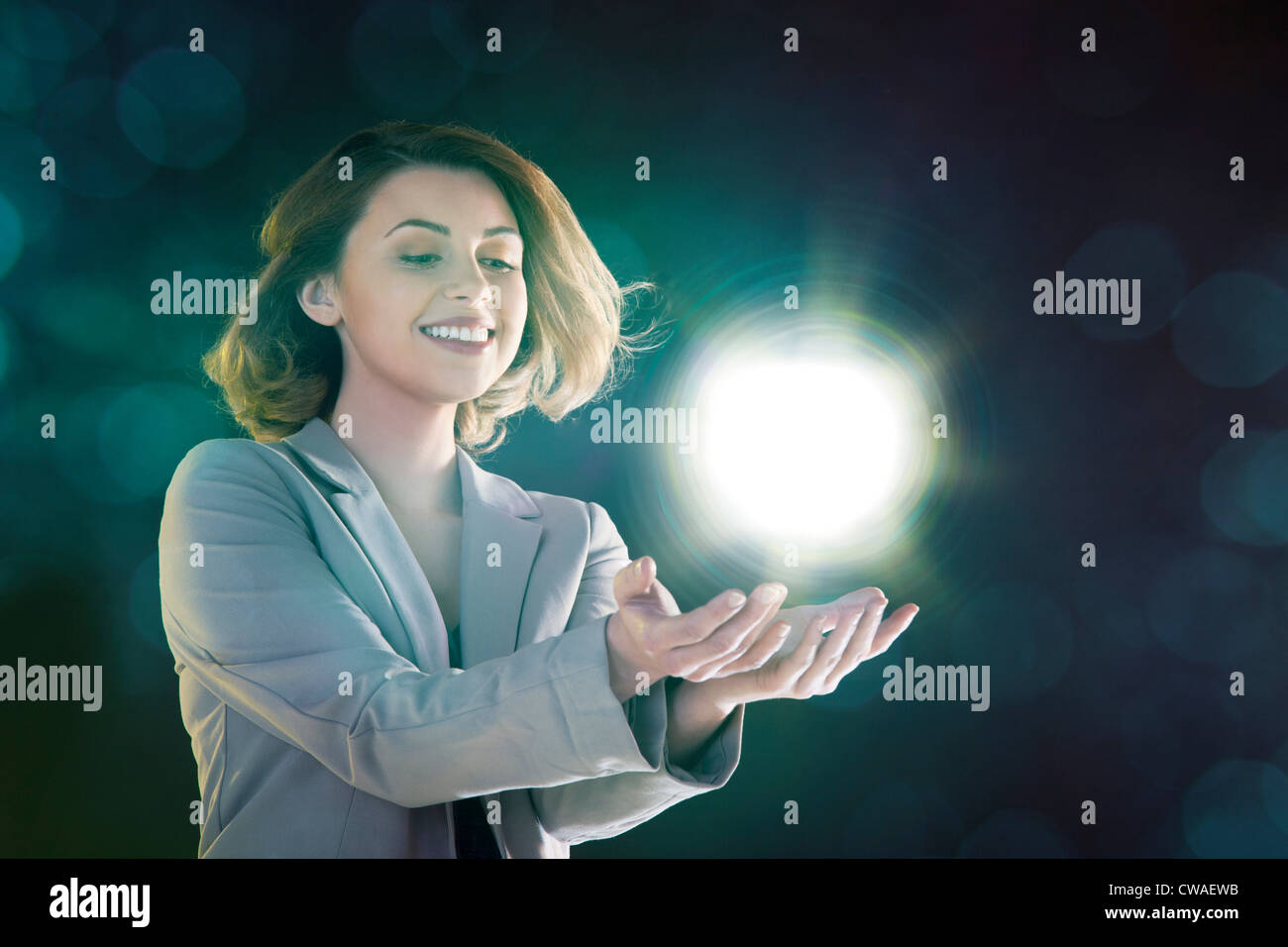 Young woman holding ball of light - Stock Image