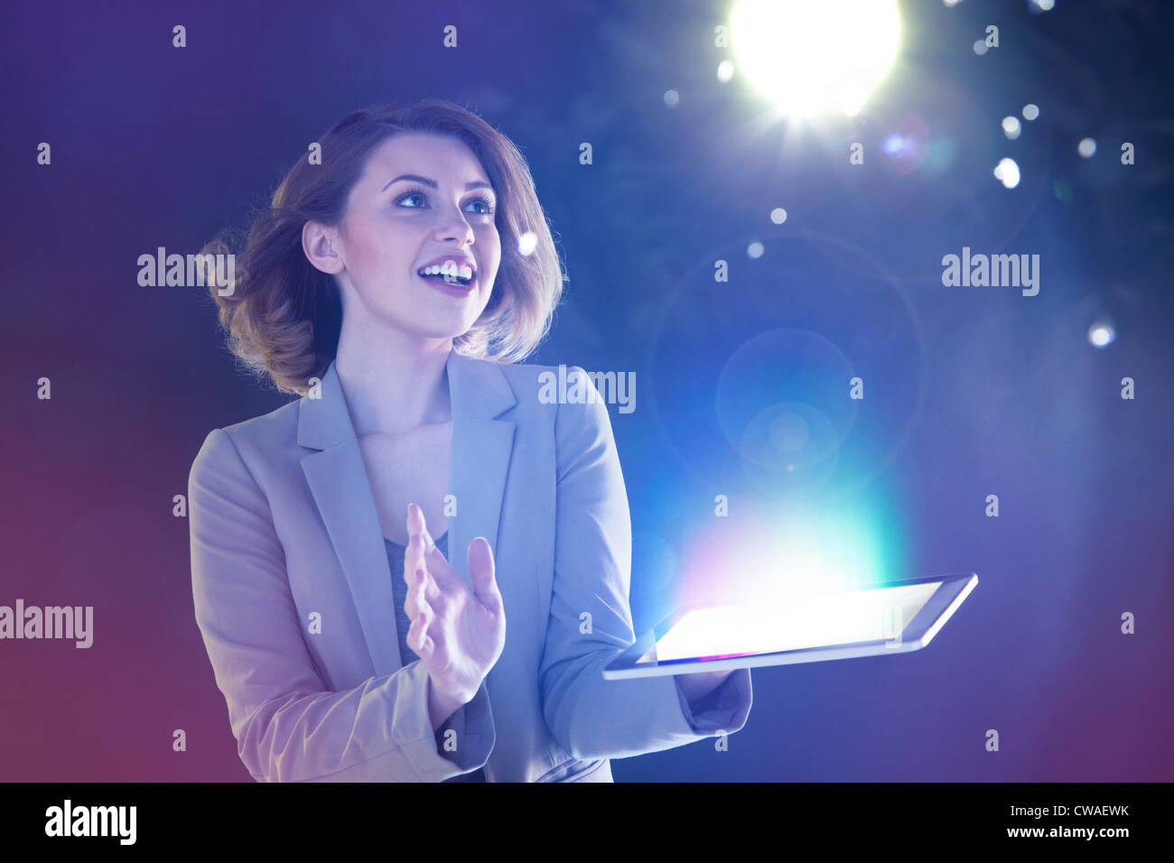 Young woman looking at lights coming from digital tablet - Stock Image