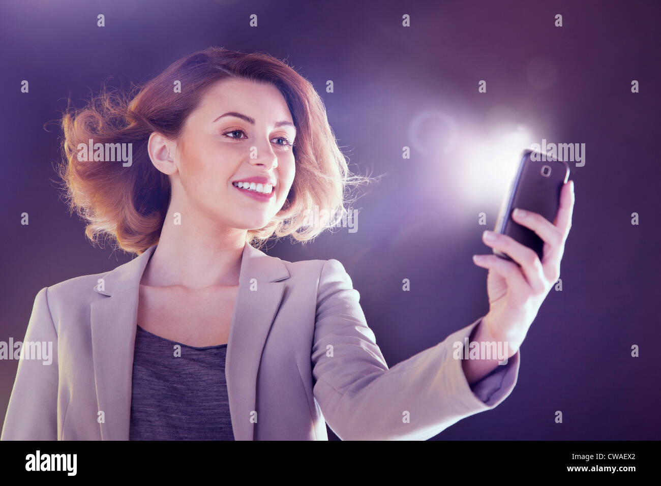 Young woman looking at cellphone with lights - Stock Image