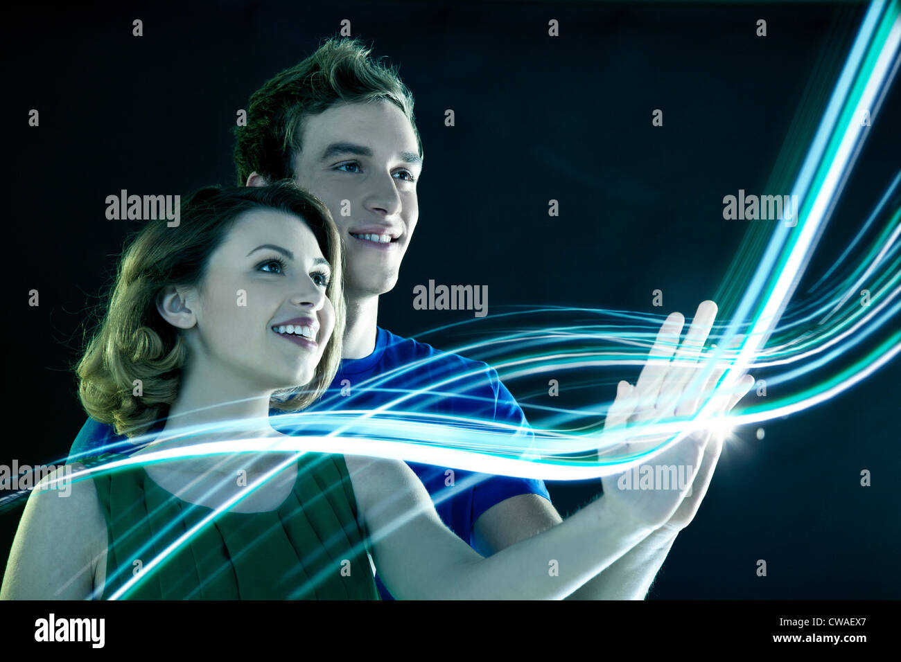 Young couple touching streams of light - Stock Image
