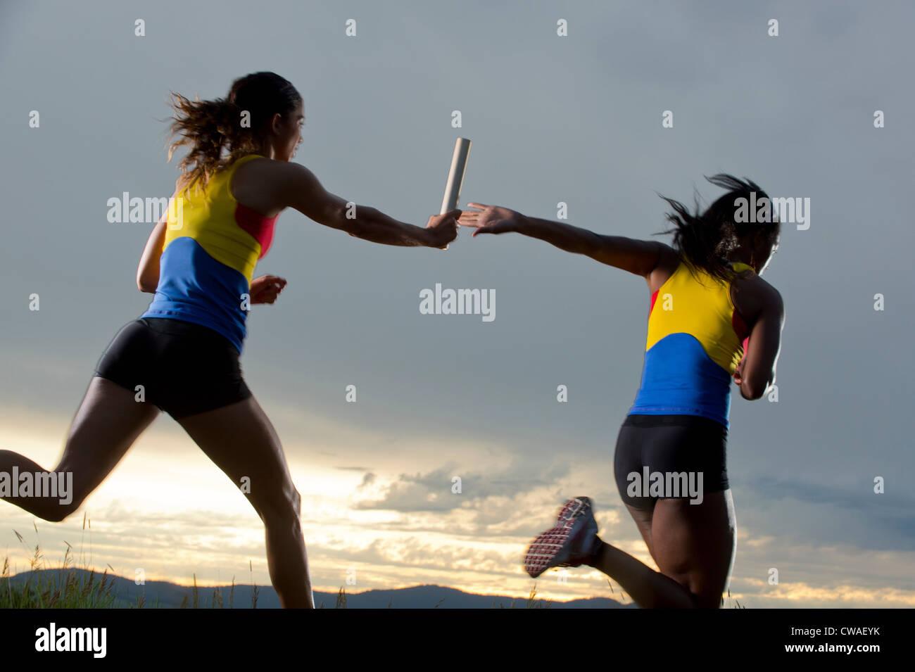 Female relay racers passing baton - Stock Image