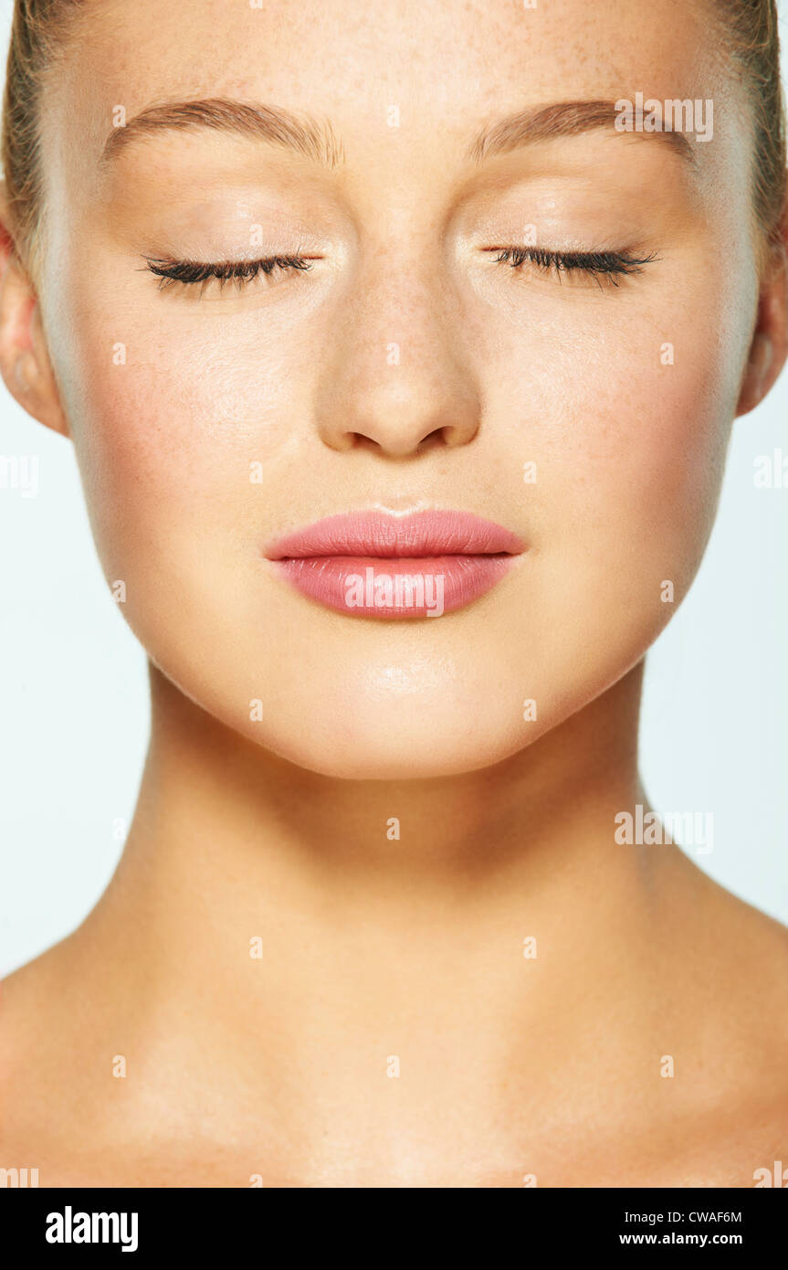 Close up on face of young woman with eyes closed - Stock Image