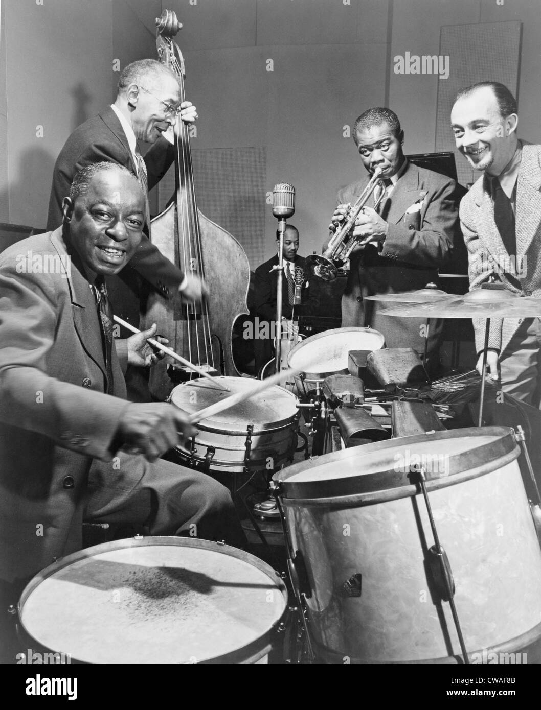 """Louis Armstrong (1901-1971), playing trumpet with others during a 1947 broadcast of """"This is Jazz"""" radio show, directed by Rudi Stock Photo"""