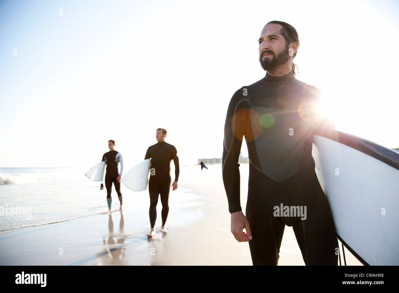 Three surfers at beach - Stock Image