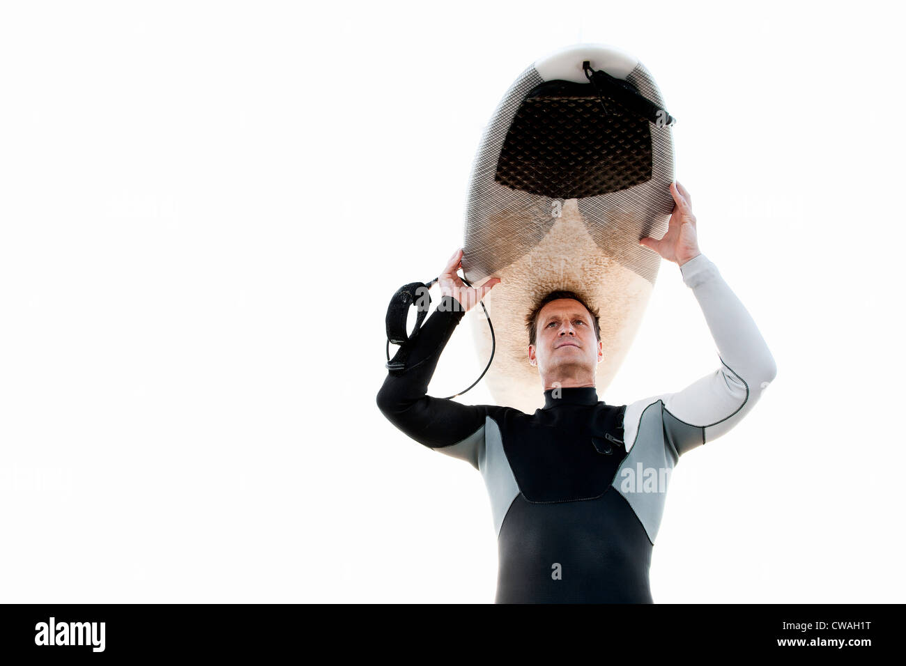 Surfer carrying surfboard on head - Stock Image