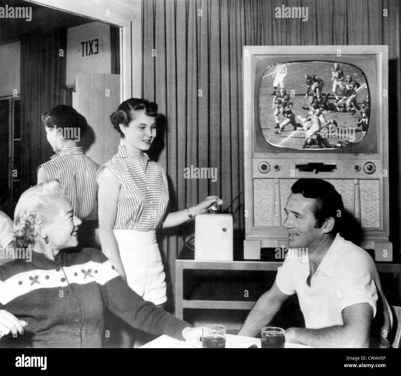 Mrs. Hal Roach Jr., Shari Roach, Howard Duff watch closed circuit broad cast of Notre Dame-Southern California football - Stock Image
