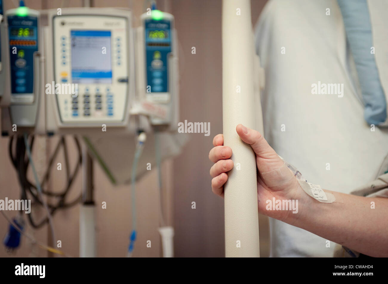 Woman gripping hospital bed with hand - Stock Image