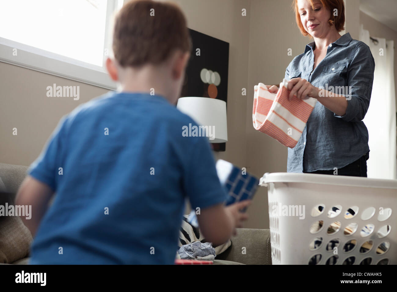 Mother sorting laundry, son playing - Stock Image