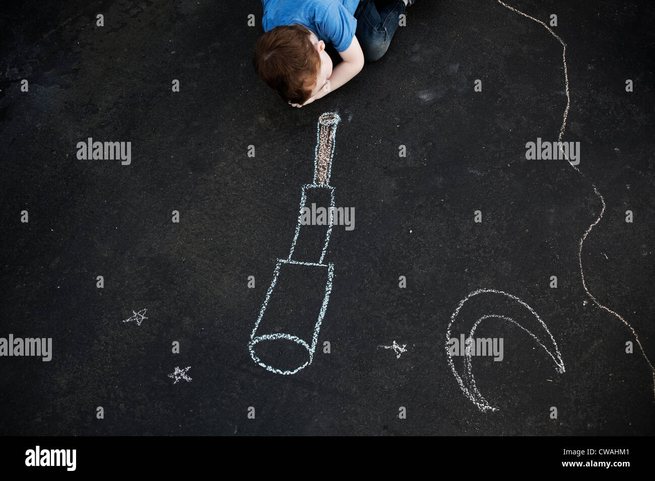 Boy on floor looking at chalk drawing - Stock Image