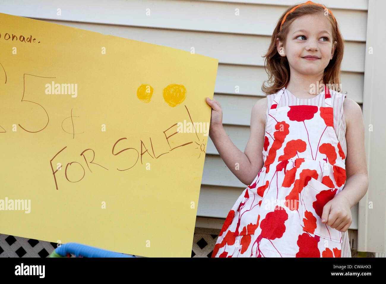 Girl holding homemade lemonade for sale sign - Stock Image