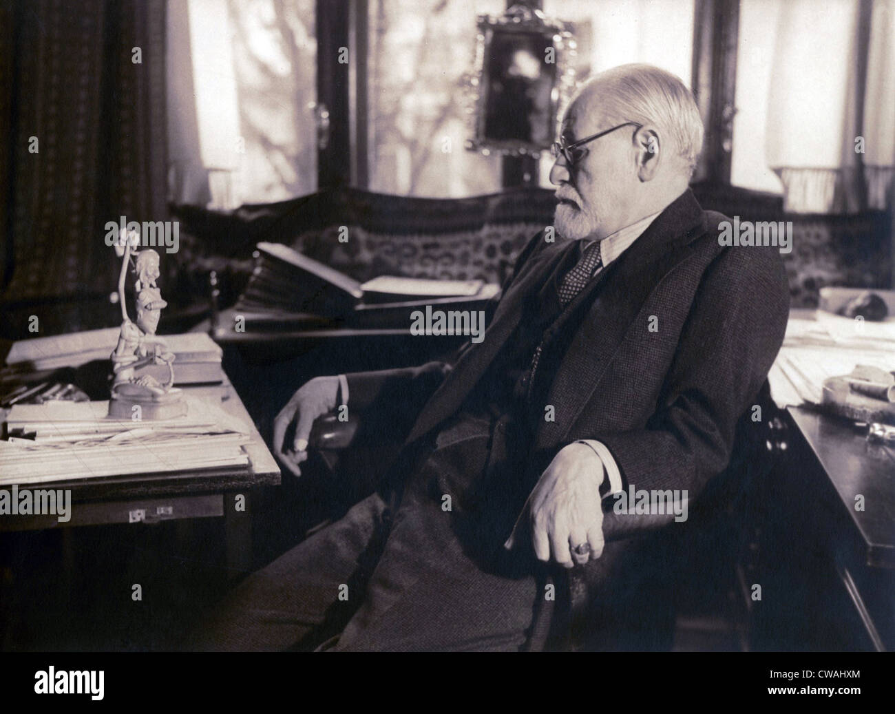 Sigmund Freud seated in his study contemplating a carved figurine (possibly Javanese) on his desk in 1937 photography - Stock Image