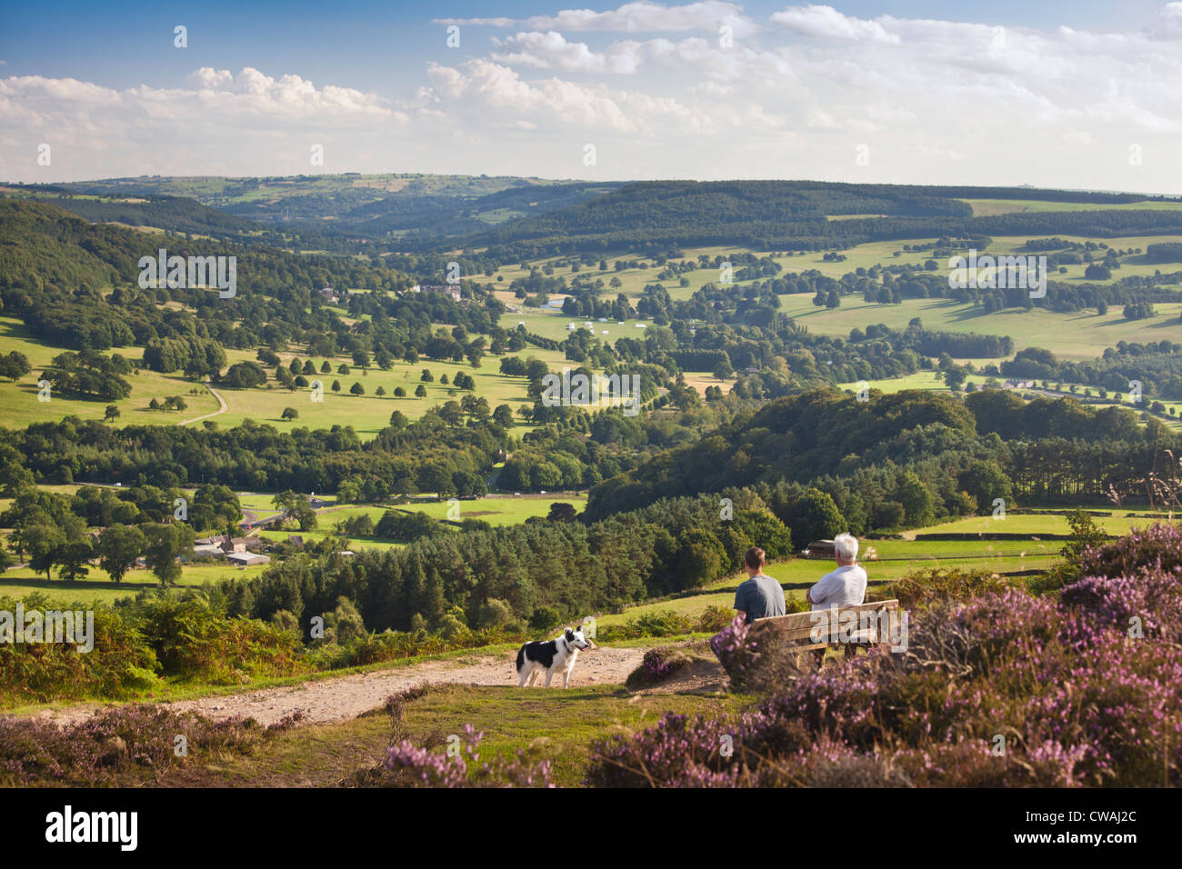Walkers admire the view from Baslow Edge over the Derwent Valley and Chatsworth Park, Derbyshire, England, UK - Stock Image
