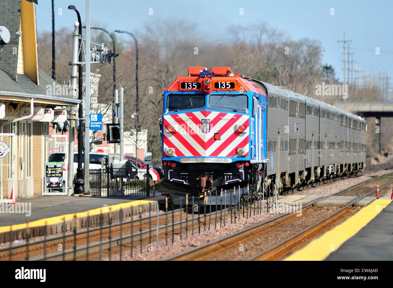 Metra commuter train departs the Geneva, Illinois station on St. Patrick's Day headed to Chicago. Geneva, Illinois, - Stock Image