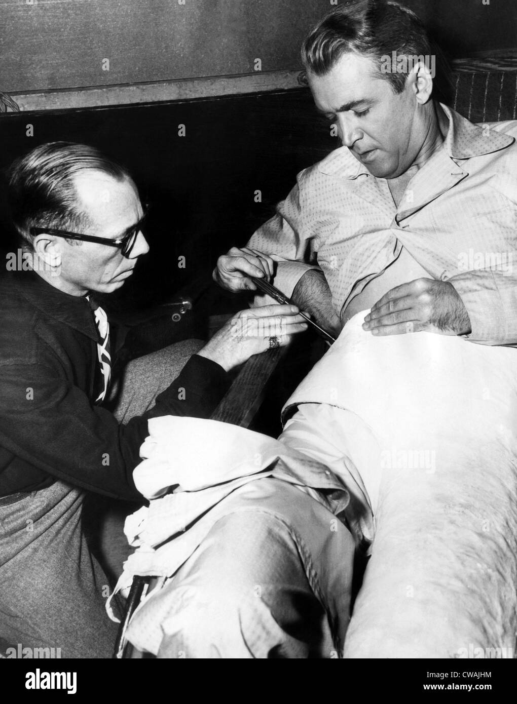 Prop man Bill Sapp screws James Stewart into a plaster cast on the set of Alfred Hitchcock's 'REAR WINDOW', - Stock Image
