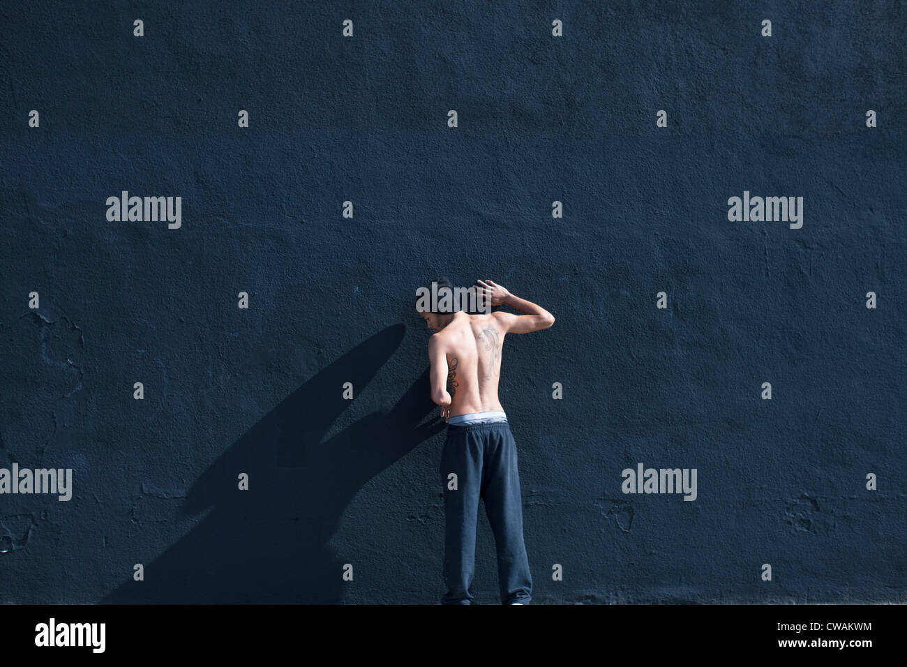 Barchested man leaning against a wall - Stock Image