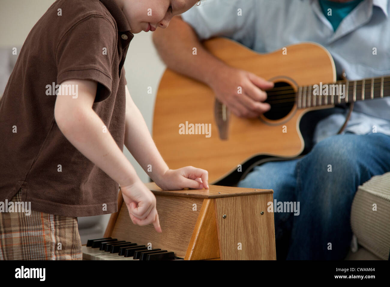 Boy playing little piano as man plays guitar - Stock Image