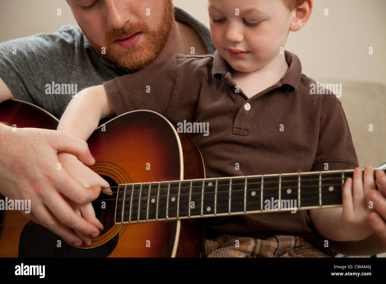 Father teaching son to play guitar - Stock Image