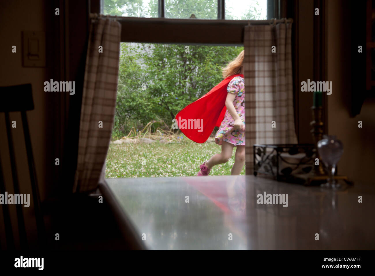 Girl in a cape running past an open window - Stock Image