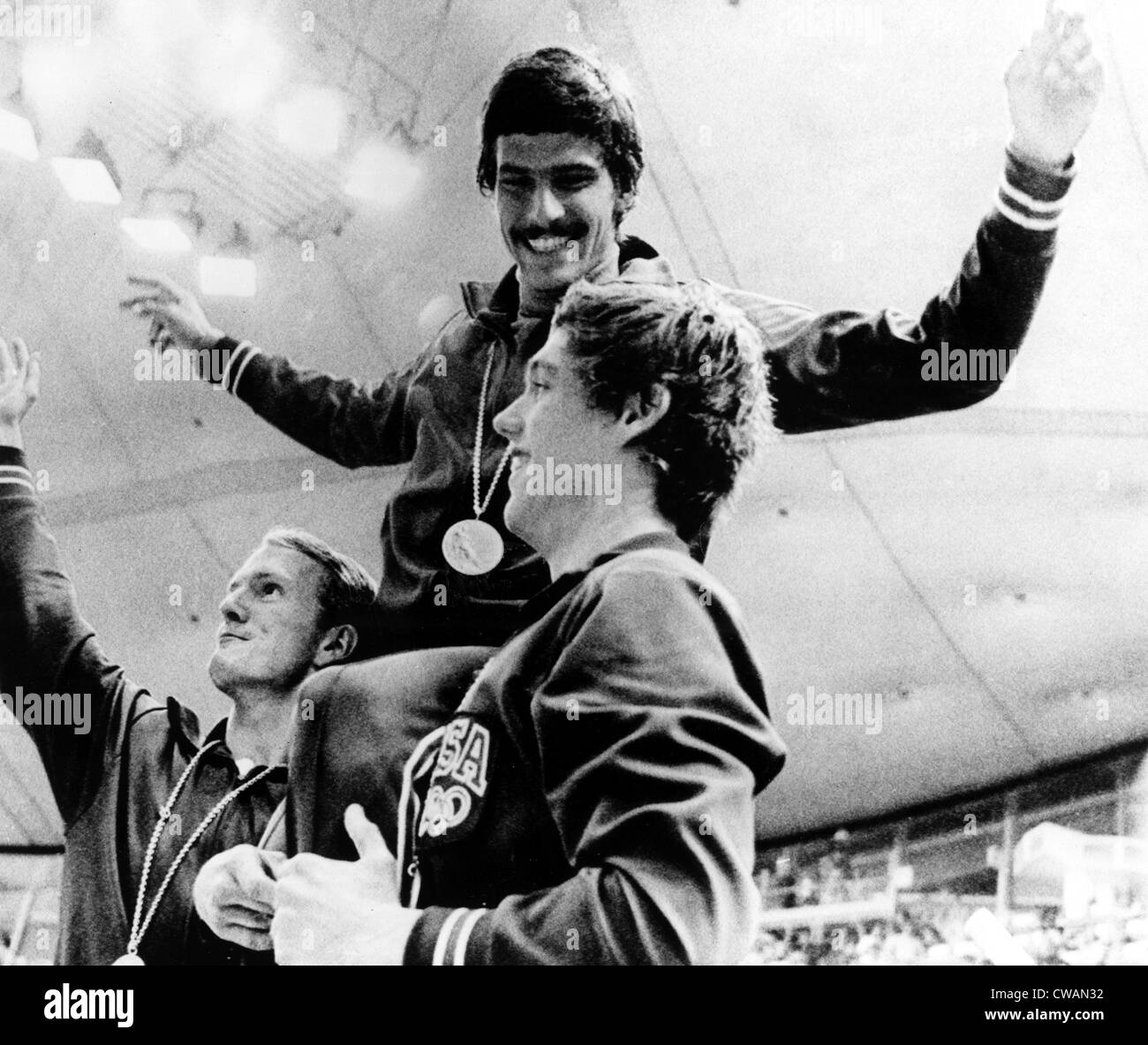 Mark Spitz shows off his 7th Gold Medal, supported by teammates Tom Bruce (L) and Mike Stamm (R), following the - Stock Image