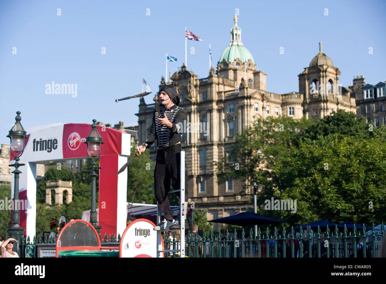 A Edinburgh fringe street busker juggling in front of the Bank of Scotland. - Stock Image