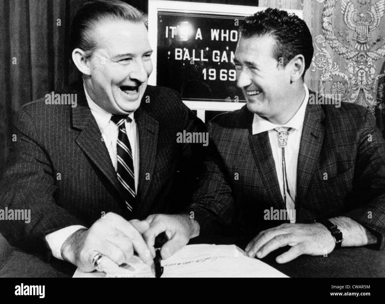 Robert Short, owner of the Washington Senators laughs as he signs Ted Williams to a five-year contract as manager - Stock Image