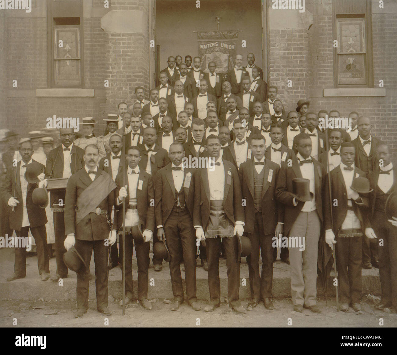 Formally dressed African American men pose with derbies and top hats, and banner labeled Waiters Union in Georgia, - Stock Image