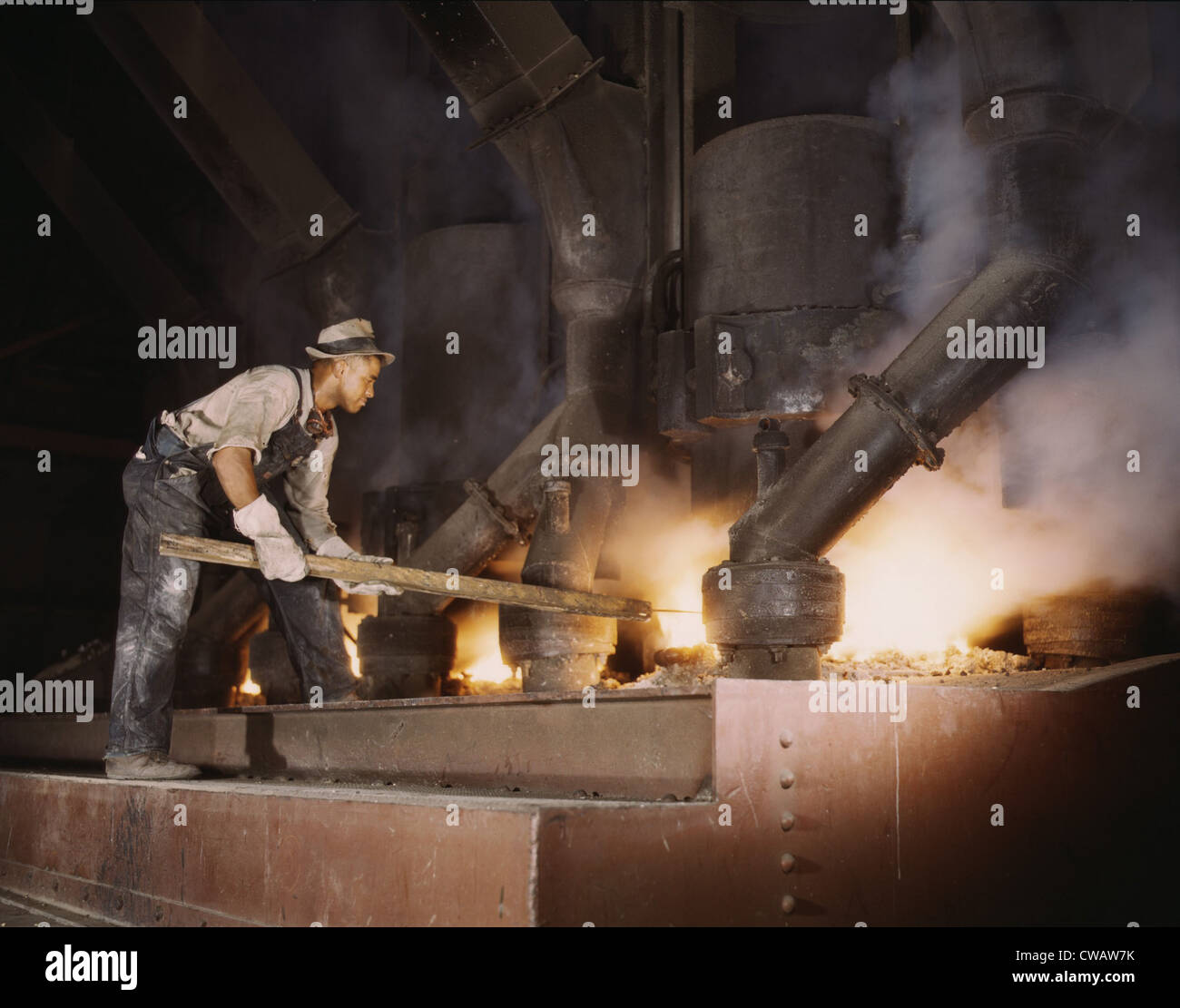 African American worker at an electric phosphate smelting furnace used to make elemental phosphorus for the World - Stock Image