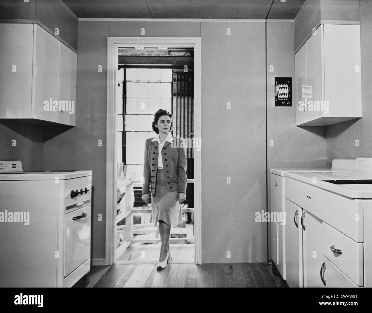Women enters a modern 1940s kitchen with white enameled metal cabinets.  The housing was built by the government Stock Photo