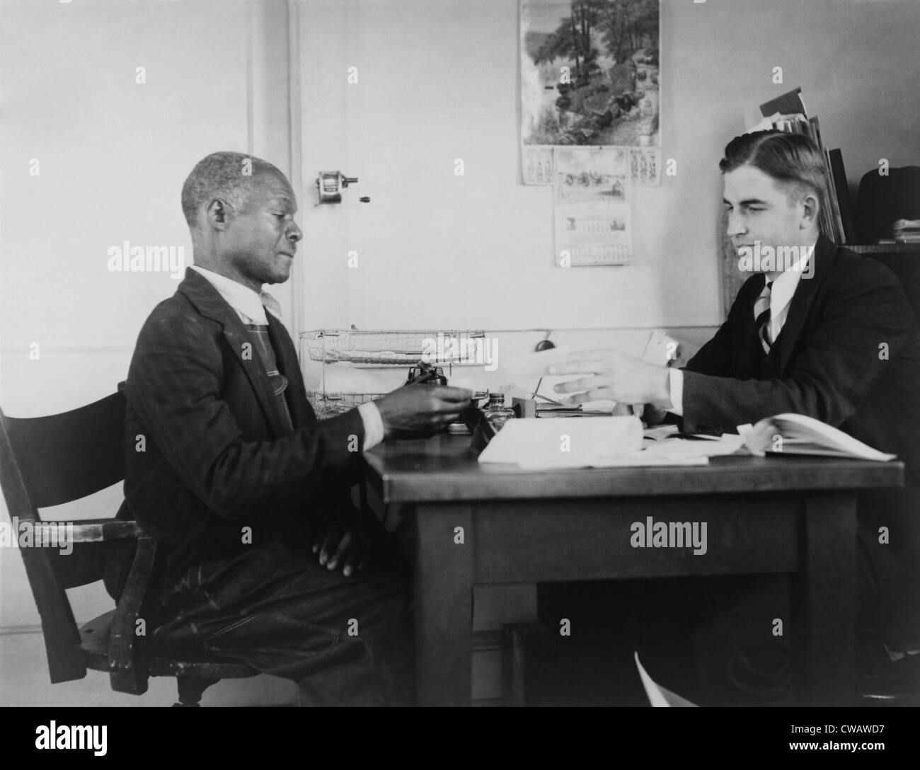 An African American farmer repays his Farm Security Administration (FSA) loan. The New Deal agency provided guidance - Stock Image