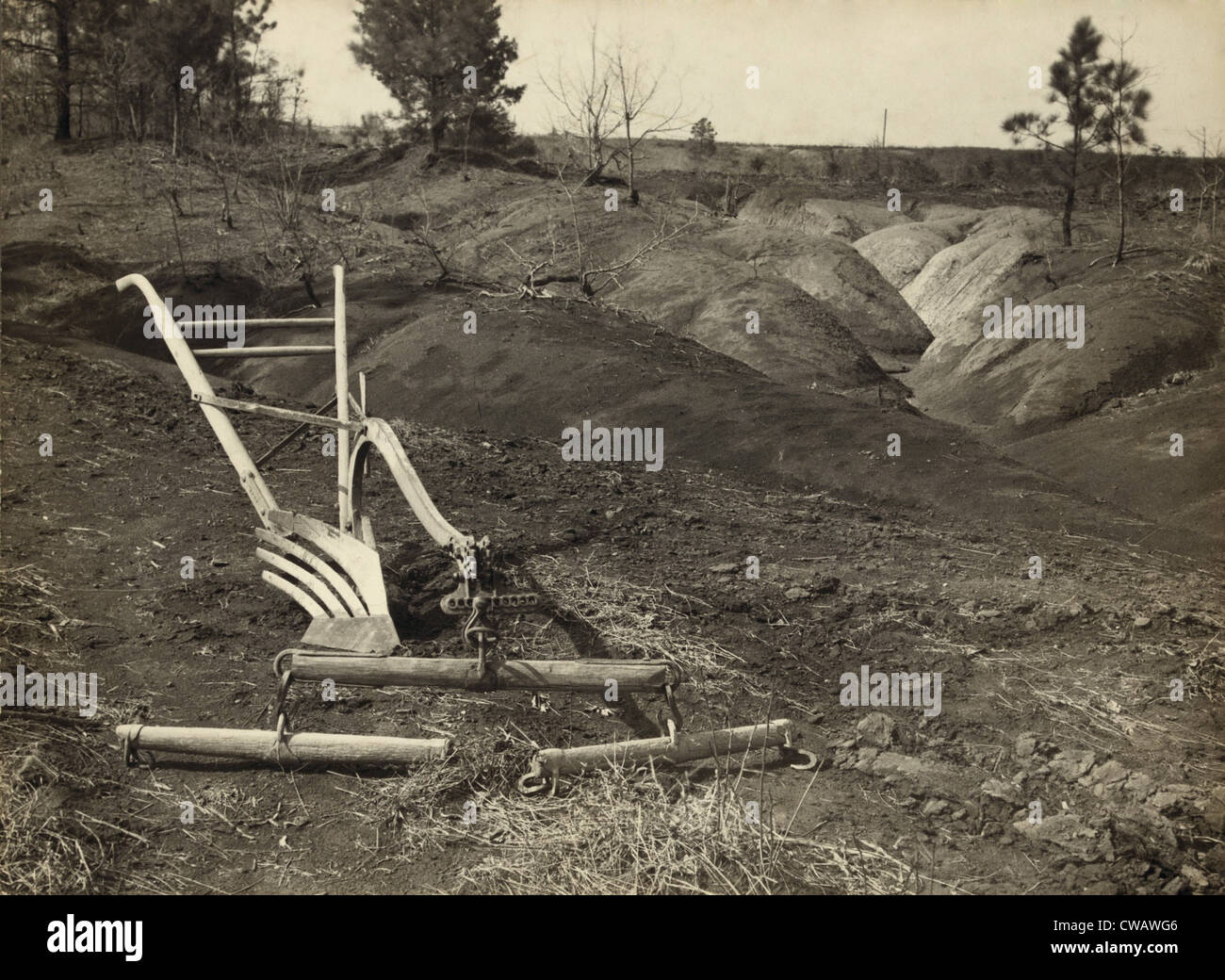 An idle plow on farm land adjacent to eroded land in Jackson County Alabama.  The New Deal established agricultural - Stock Image